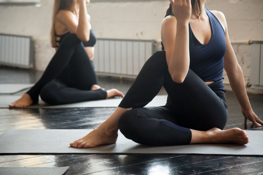 group-young-sporty-people-ardha-matsyendrasana-pose-close.jpg